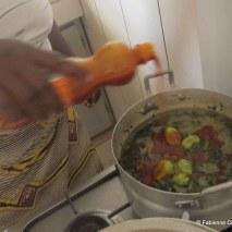 Remettez sur le feu, ajoutez un bon trait d'huile rouge, les piments broyés et d'autres entiers, les crabes, le poisson et un cube de bouillon.